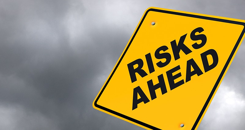 """Yellow sign that reads """"Risks Ahead"""""""