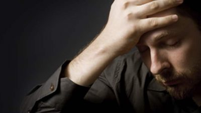 Man with hand on forehead looking distraught