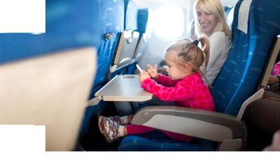 Mom and child smiling in coach seats