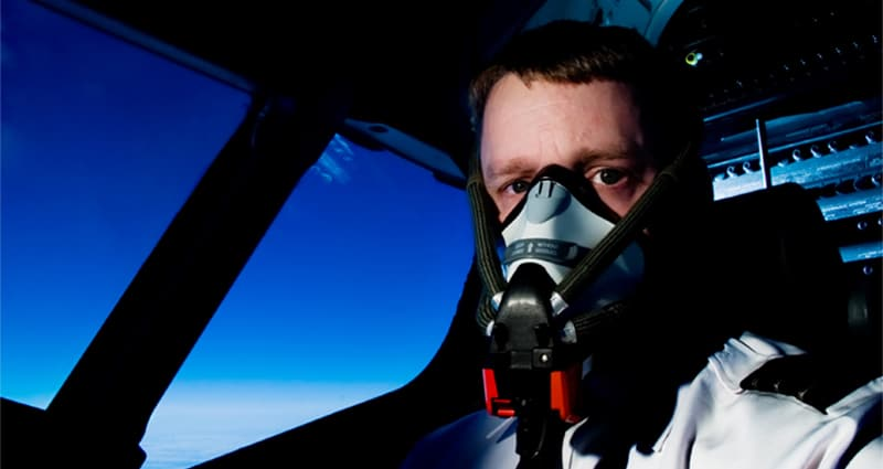 Pilot wearing oxygen mask in cockpit