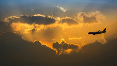 Plane flying in clouds during sunset