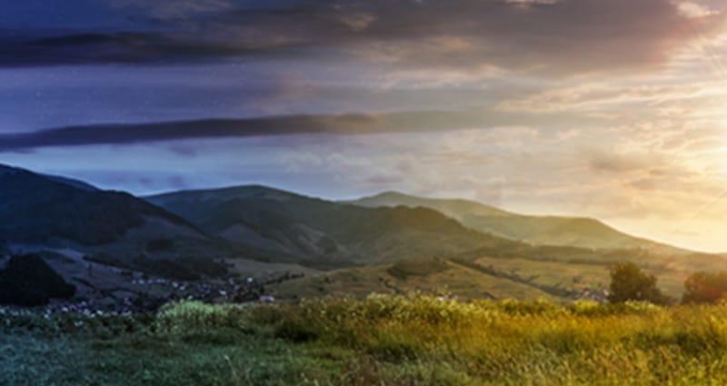 Mountain range behind fields during sunset
