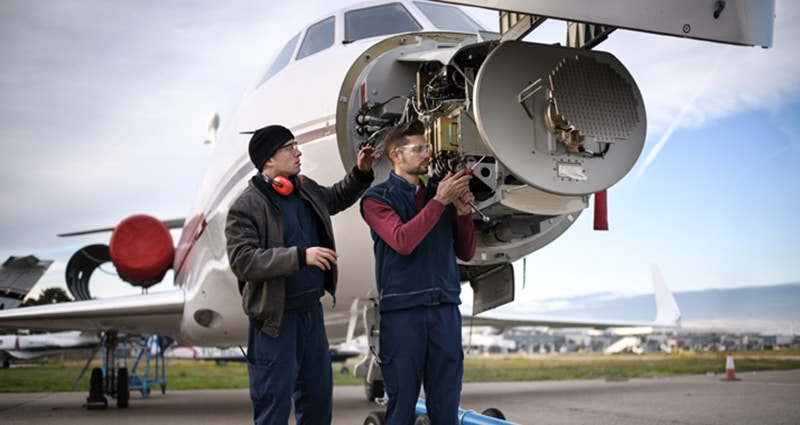 Two technicians working on front of plane