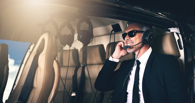 Business man with sunglasses smiling in plane