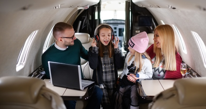 Family of four smiling on plane