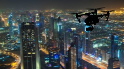 Drone flying at night above large city