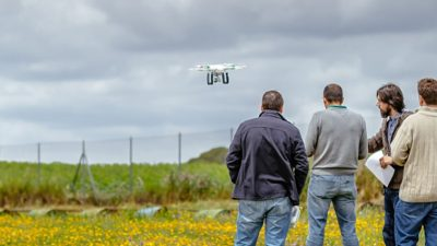Group of four men flying drone in a field