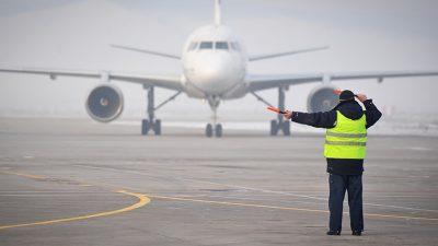 Aircraft marshaller signaling plane to turn