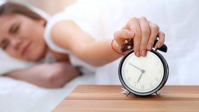Woman hitting snooze on her alarm clock