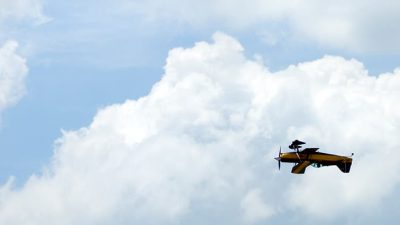 Small plane flying upside down in clouds