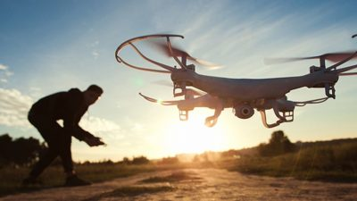 Man flying drone at sunset