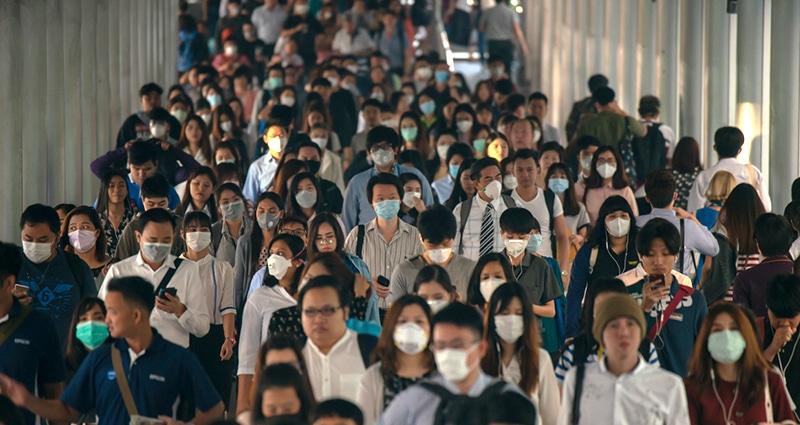 Dozens of masked travelers walking