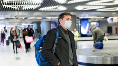 Man wearing face mask waiting for luggage