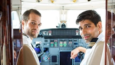 Two pilots smiling from the cockpit