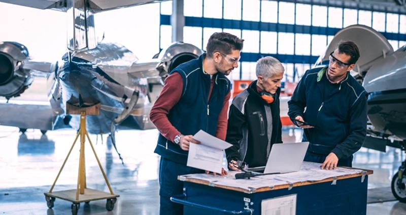 Technicians studying blueprints in hangar
