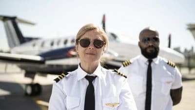 Woman and man pilots standing on runway