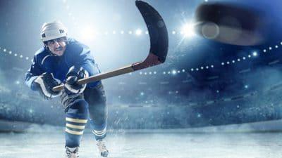 Hockey player on ice shooting puck