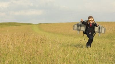 Boy running through field with toy wings