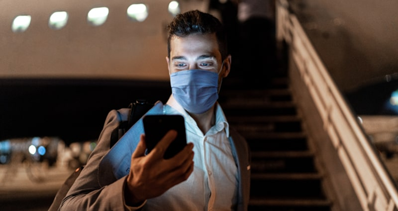 Man wearing face mask checking his phone before boarding plane