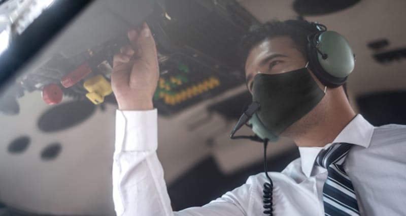 Pilot wearing face mask completing preflight checklist