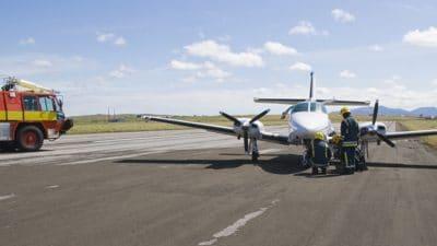 Emergency crew assisting plane on runway
