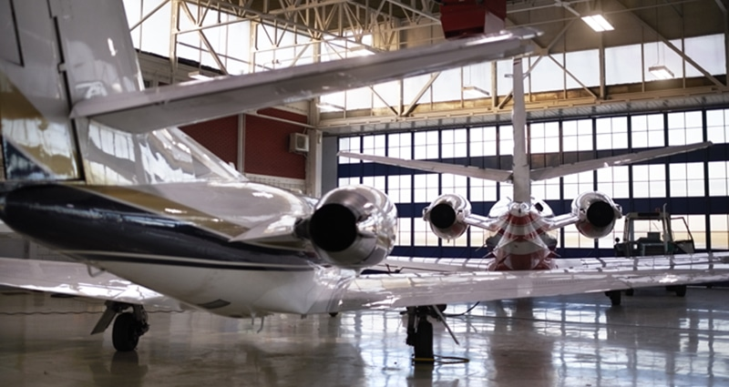 Two parked airplanes glistening in a well-lit hangar