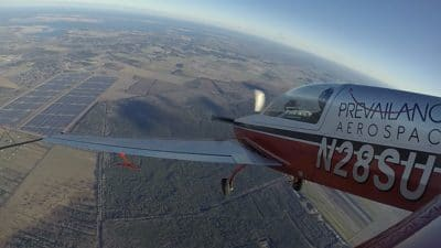 Small plane flying above solar farm